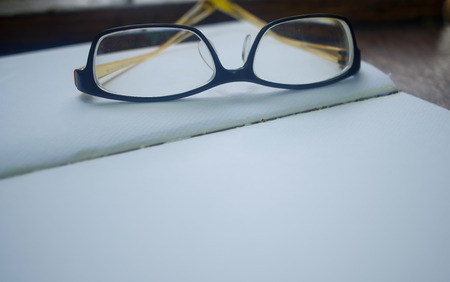 closeup open empty notebook with glasses on wooden table photo
