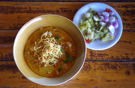 Northern Thai Noodle Curry Soup in bowl serve with lemon , onion and pickle vegetable put on the wooden table, Selective focus photo