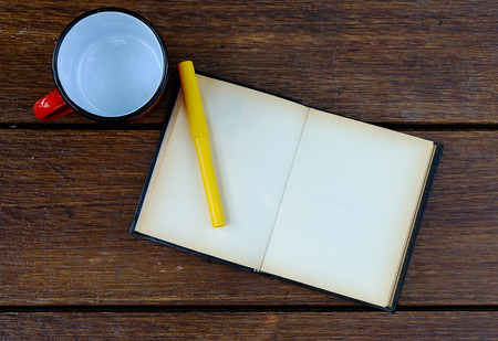 open blank old notebook on wooden table with empty red cup and yellow pen photo