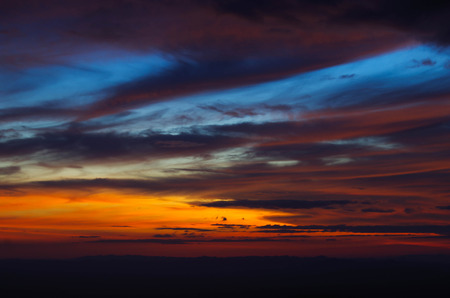 red sky: dark cloud and red sky before sunset over the mountain Stock Photo