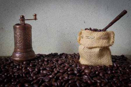cocoa bean: Turkish coffee grinder and little gunny-bag lay on coffee bean Stock Photo