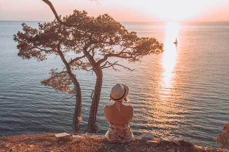 aéroglisseur: girl sitting by the sea at sunset and looking at a passing boat, in a light summer dress and hat on the mountainside. She looks at the sea. Nearby stands a tree and the sun sets over the horizon