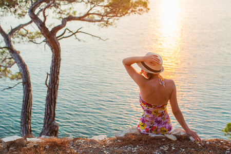 girl sitting by the sea at sunset and hat holds hands in a light summer dress and hat on the mountainside. She looks at the sea. Nearby stands a tree and the sun sets over the horizon Stock Photo