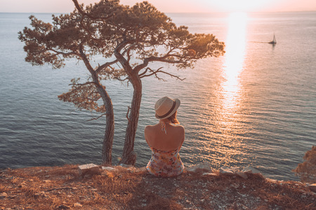girl sitting by the sea at sunset and looking at a passing boat, in a light summer dress and hat on the mountainside. She looks at the sea. Nearby stands a tree and the sun sets over the horizon