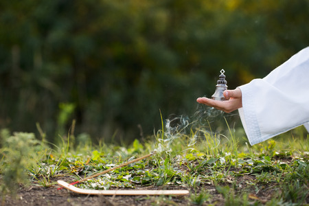 boy in a kimono holds a burning incense stick and a Buddhist bell, performing a mysterious rite. Meditation, concentration, religion topic