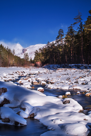 sunrise on the winter mountain river, among the snow-covered rocks and snow-capped mountain peaks in the background. smeared water from fast flow