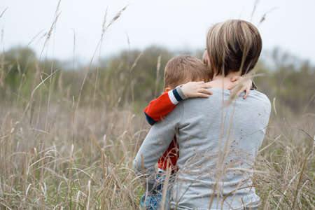 A young mother and her little son warmly embrace each other calmly and sensually, thinking among the dry grass.