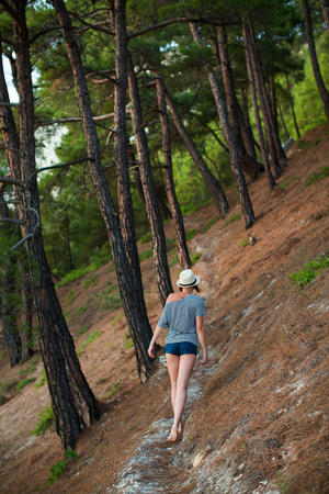 woman walking along a path in the summer forest, with a hat on his head, in shorts and a striped T-shirt, vest. With his back to the camera. Stock Photo