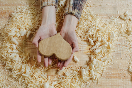 A wooden heart in the gentle hands of a girl on a wooden bench among the sawdust. Handmade on wood