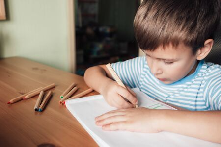 Cute boy sits at desk and draws in album with colored pencils, lifestyle