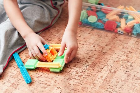 A close-up of a child playing with a needle constructor which helps to growth imagination and massages his fingertips, developing fine motor skills.