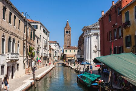 VENICE, ITALY - JUNE 19, 2019 View to the Church of Saint Barnabas and its bell tower on Campo San Barnaba. Rio de S.Barnaba chanal with floating market boat selling vegetables and fruits Editorial