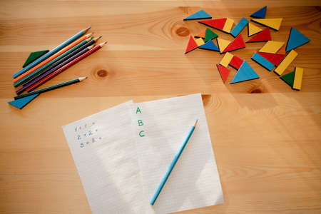 sheets of paper with math and writing tasks on a wooden table, concept of home learning , top view