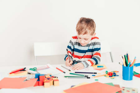 Cute child study drawing at the table, colored pencils and paper around Banque d'images