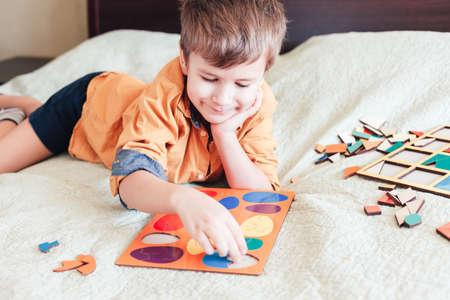 Cute child boy collects wooden puzzle in the form of Easter eggs on bed