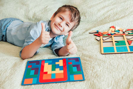 happy boy sits on the bed and lays puzzles. Child looks at the camera and shows thumbs up