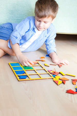 Cute happy boy sits on floor and lays puzzles