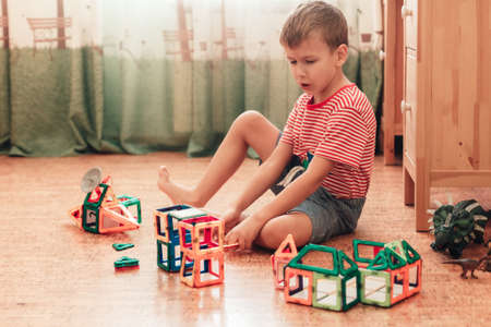 A boy plays with magnetic constructor in children room sitting on cork floor