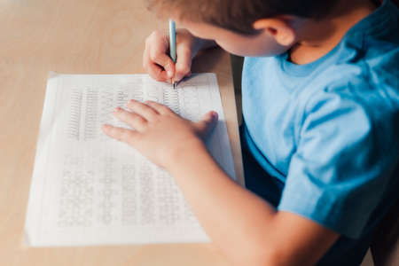 Close up of cute child doing his homework. Kid writing different lines by pencil. Children education concept. Stock Photo
