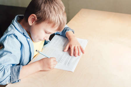 Close up of cute boy doing his homework. Kid writing different lines with pencil. Children education concept. Stock Photo