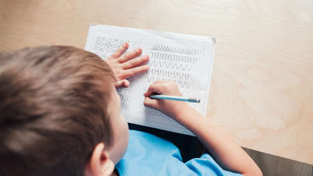 Child boy writing different lines with pencil. Prewriting practice to prepare hands for write letters. Children education concept. View fron above