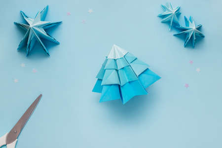Simple origami 3D Christmas tree, step 20. Match the details from the largest at the bottom to the smallest at the top. You can use glue to hold it in place or leave it as it is to keep the tree lush.