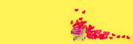 Trolley shopping cart filled with a lot of hearts on pink background. Concept of shopping for Valentines Day. Copy Space for text.