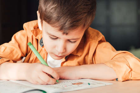 Cute 7 years old child doing his homework sitting by desk. Boy writing in notebook.
