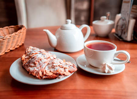 White cup with hot tea, teapot and tasty croissant on plate on wooden table in cafe in the morning Фото со стока