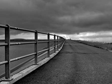 railing at the dam reservoir with dramatic sky and water