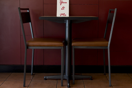 drink me: Restaurant table for two with the text you and me