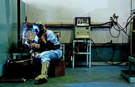 argon: welder with protective mask welding metal and has spark splash