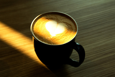 froth: Cup of cappuccino art coffee with froth shape heart and wooden background Stock Photo