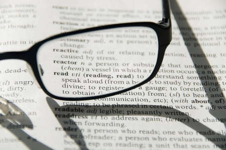 Glasses on dictionary. Focus on the definition of the word read. photo