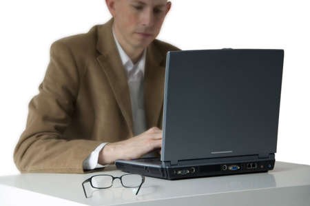 Businessman working on laptop. Focus on laptop, glasses and desk. photo