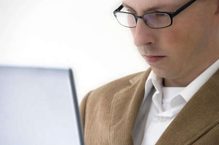 Man with glasses looking concentrated at laptop screen photo