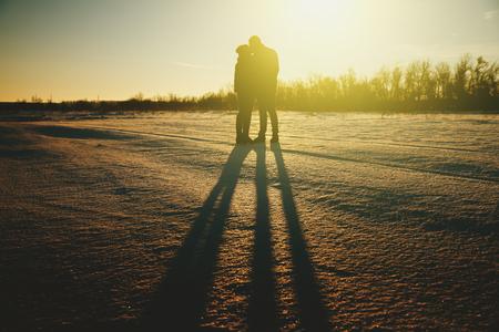 pareja besandose: Silueta de un par joven que se besa en la gente del sol