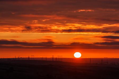 light transmission: Beautiful sunset with factory electricity on horizon Stock Photo