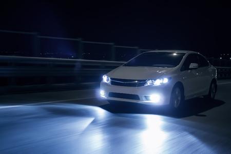 Auto mit Xenon-Scheinwerfern schnell fahren auf der Straße an nah Standard-Bild - 51261882