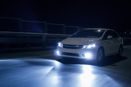 Car with xenon headlights fast drive on road at nigh