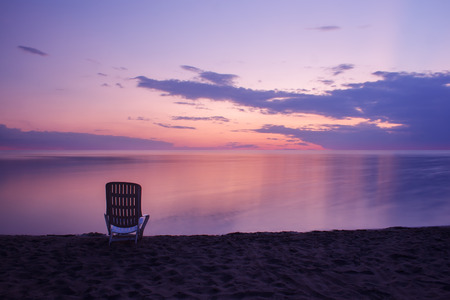 sunrise ocean: one chair standing on the beach at sunset Stock Photo