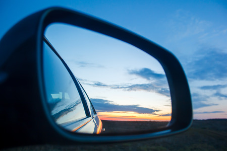 rear view mirror: Blue landscape sunset reflect in mirror of car Stock Photo