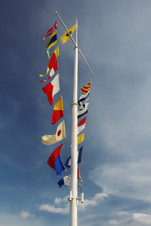 white pole: Few flags on white pole at blue cloudy sky