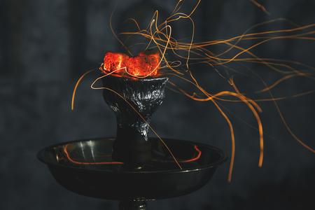 persona respirando: shisha hookah carbones al rojo vivo. Las chispas de respirar