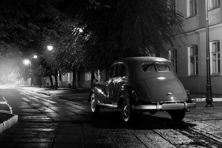 Old retro car stay on asphalt city road at rainy night
