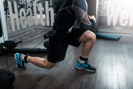 Uomo che lavora sport fitness sulla macchina tecnologica kinesis