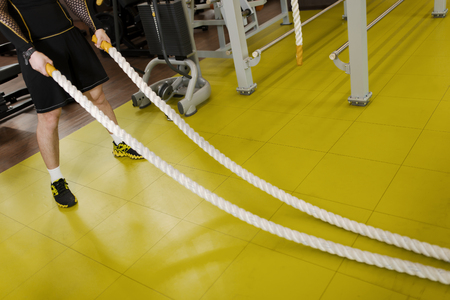battling: Man training with battle rope in fitness club