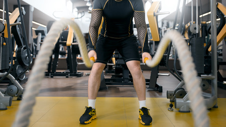 Man training with battle rope in fitness club