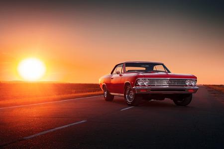 Saratov, Rusland - 7 juni 2015: Retro rode auto verblijf Chevrolet Malibu op asfalt weg bij zonsondergang