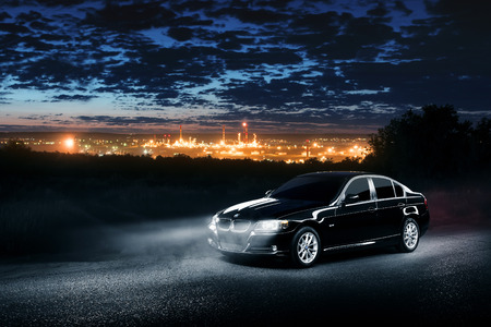 bmw: Saratov, Russia - June 12, 2015: Black car BMW E90 standing in the dark mist forest with views of the city at night Editorial